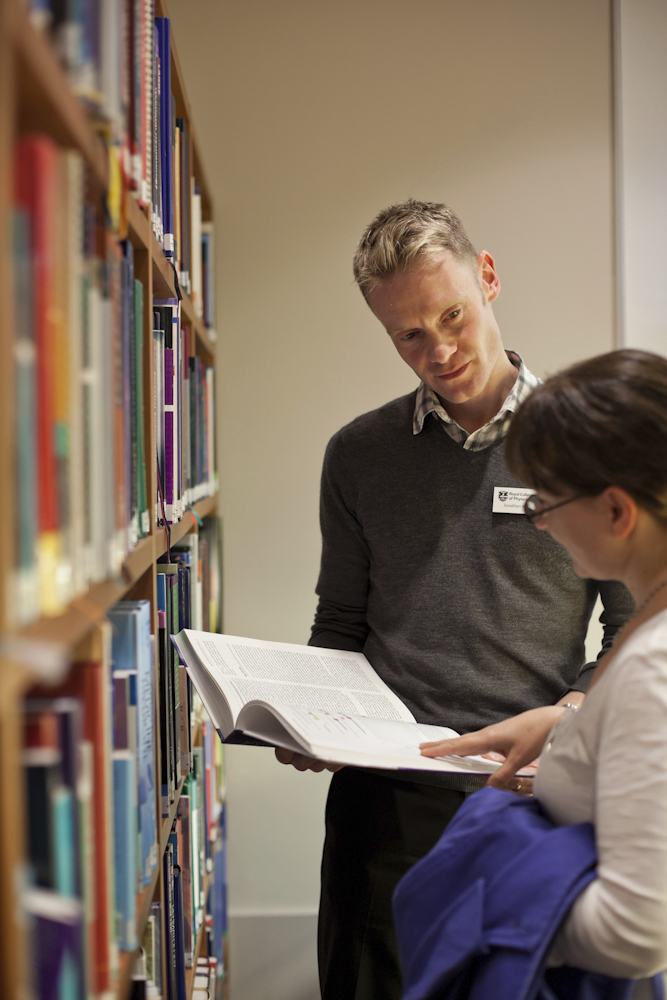 Librarian helping student in the library