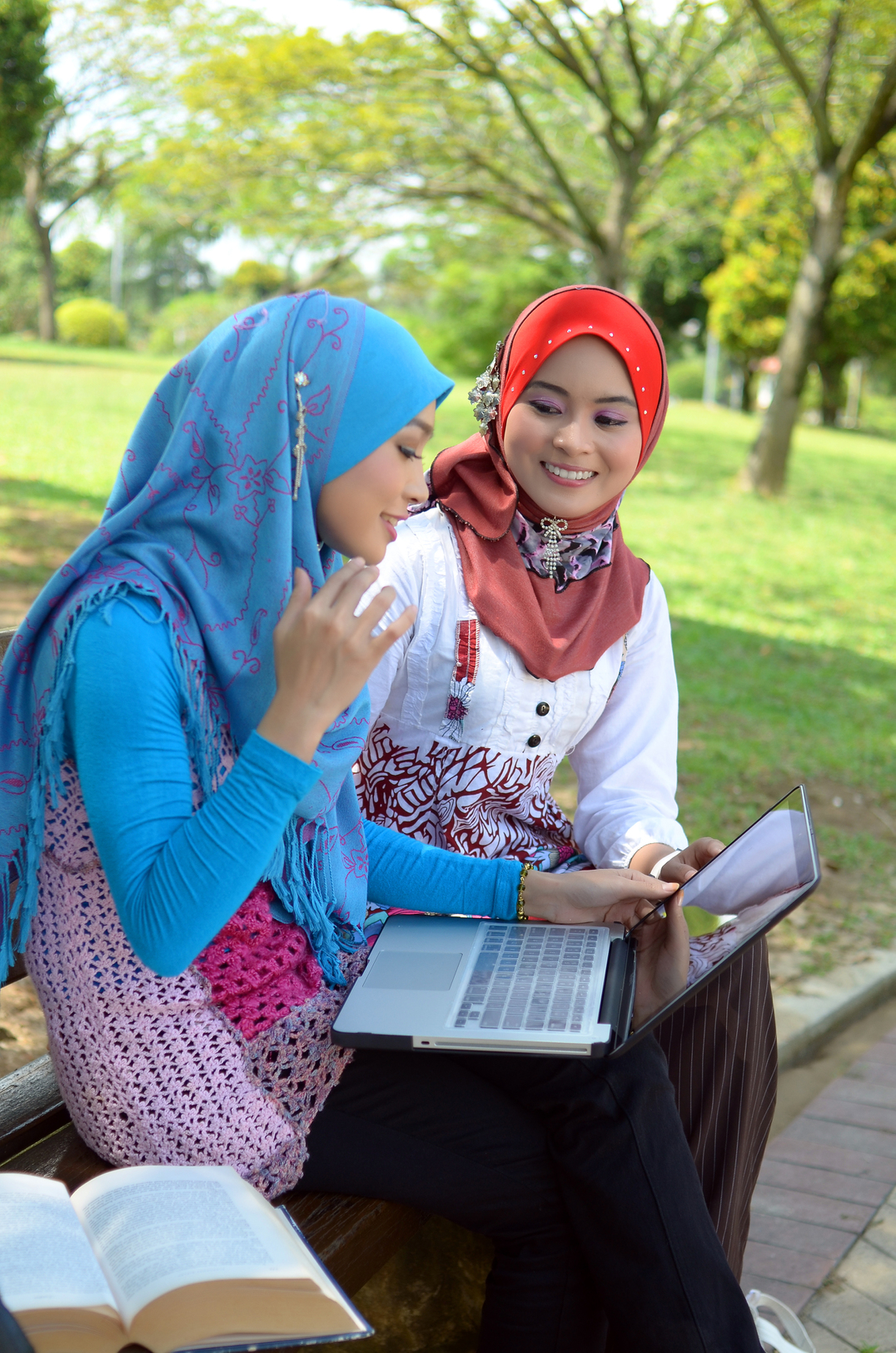 Two students studying outside with their laptops
