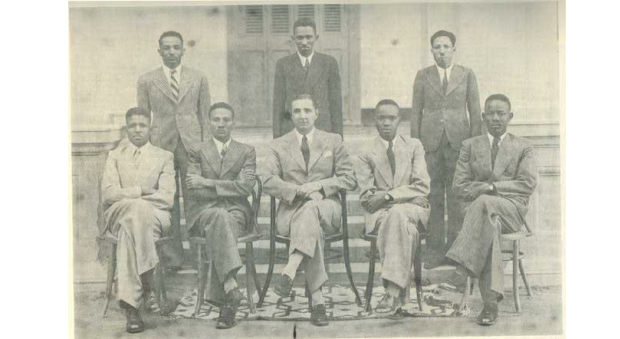 Black and white photograph of black men seated and standing for a form photograph