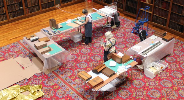 Photograph of conservators working at trestle tables inside a library
