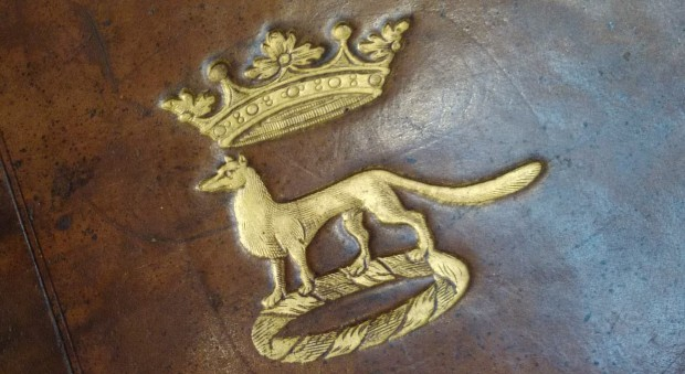 A leather book binding stamped in gold with a fox beneath a marquis's coronet.