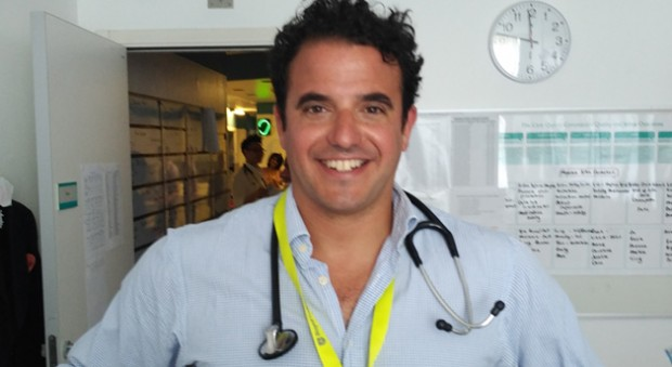 A smiling doctor with dark hair, carrying his stethoscope around his neck