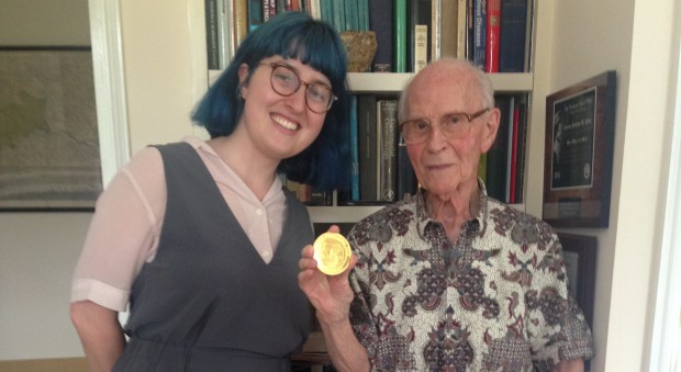 Photograph of a young woman and an older man standing next to each other. Both are smiling. The man is holding up a gold medal to show the camera.