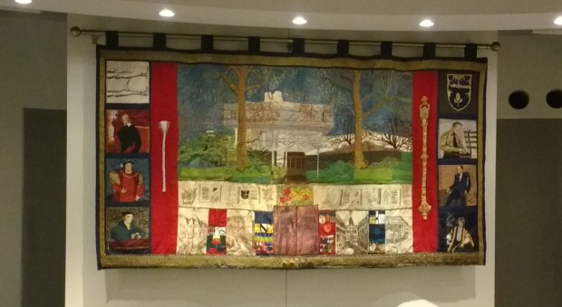 Colour photograph of a colourful rectangular tapestry depicting different faces and buildings in embroidered needlework