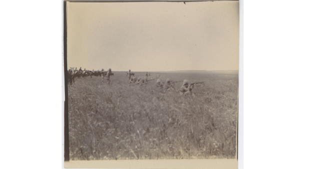 Black and white photograph of cavalry and soldiers kneeling aiming rifles