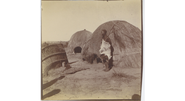 Black and white photograph of a person standing in front of a reed hut