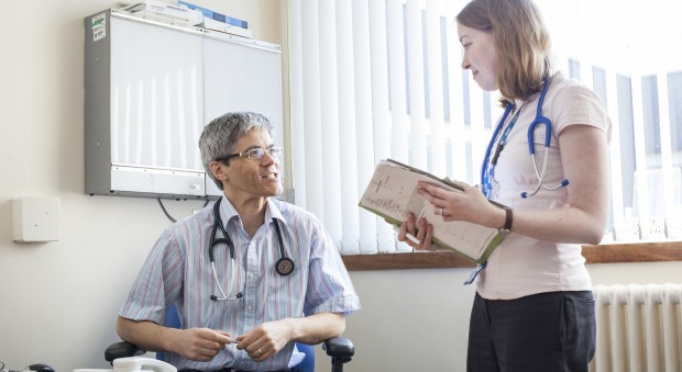 Two doctors talking, with one holding a case file