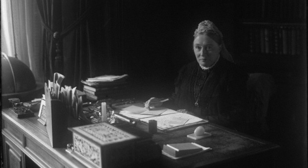 Photograph of a woman with a formal hairstyle and sombre dress sitting behind a desk