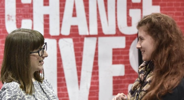 Colour photograph of two women talking to each other in front of a banner saying Museums Change Lives