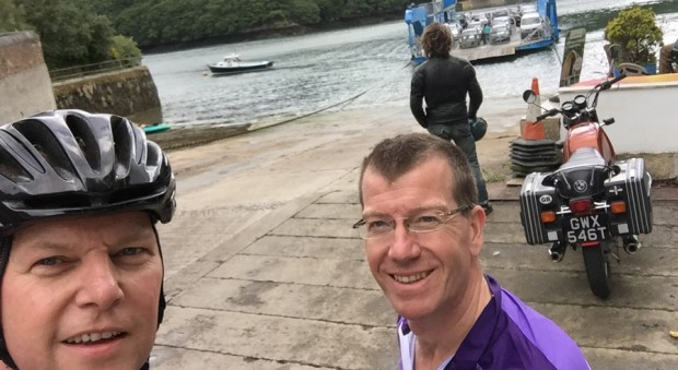 Two cyclists wait next to a river as a ferry approaches in the background