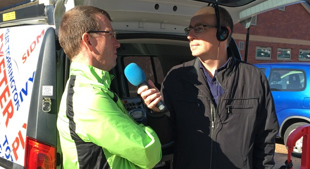 A man in a high-visibility jacket speaks into a blue microphone held by a radio interviewer.