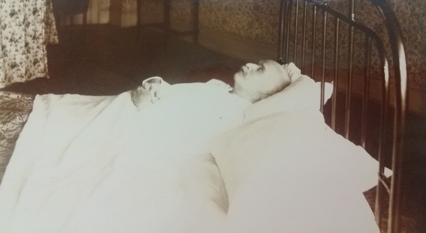 Black and white photograph of a white man with a white moustache lying in a bed with his eyes closed. Some of a room is visible behind the bed.