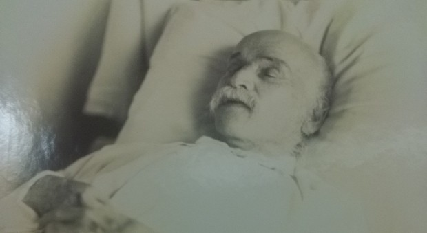 Black and white photograph of a white man with a white moustache lying in a bed with his eyes closed.