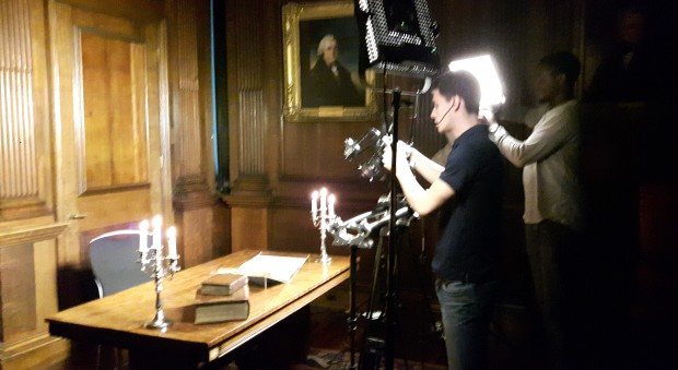 Photograph of a film crew recording rare books
