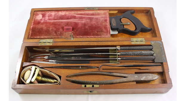 Wooden box containing surgical instruments including a saw and knives
