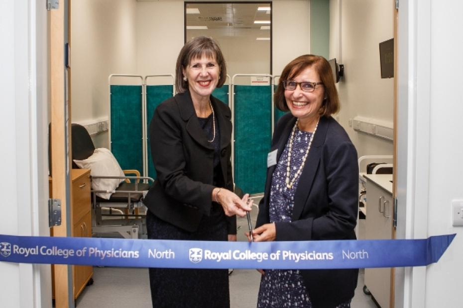 Two women cut a ribbon across the entrance to a workspace