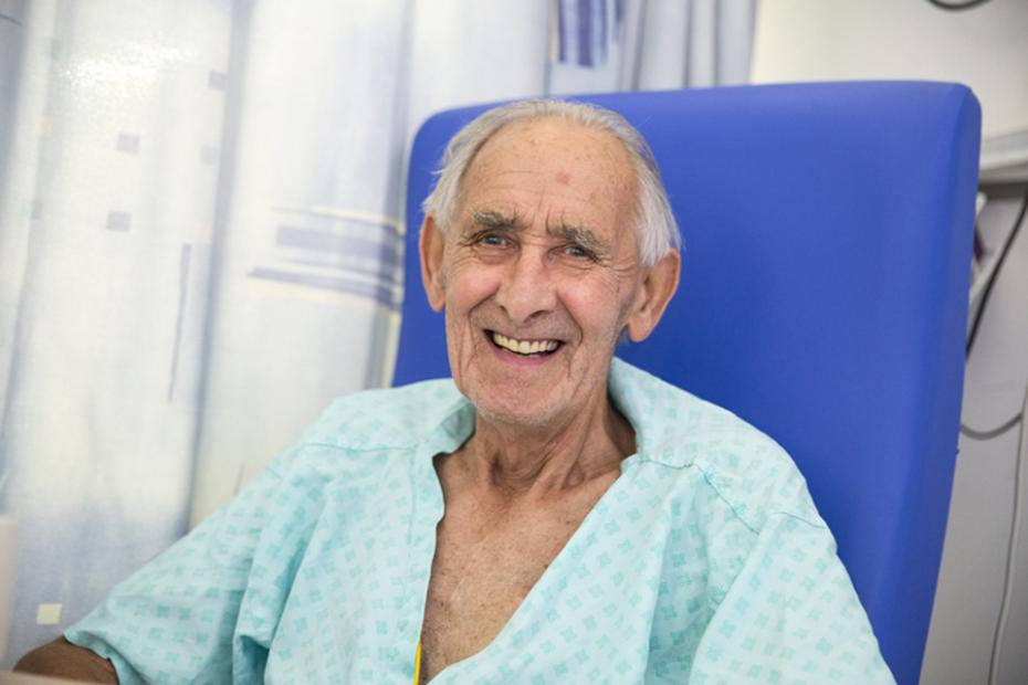 A male patient smiling in a hospital bed