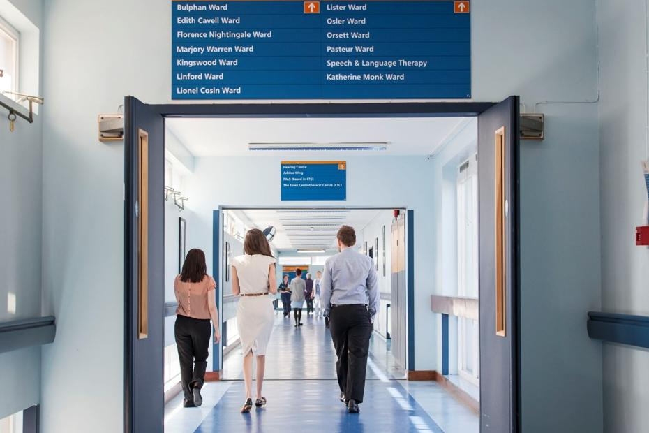 Two people walk along a hospital corridor with their backs to the camera