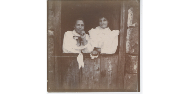Black and white photograph of two white women looking out of a window