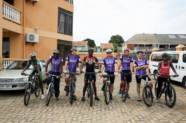 Eight people stand with their bicycles for a group photograph