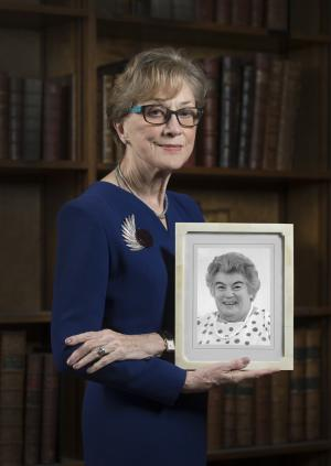 Professor Dame Carol Black holding a photograph of her inspiration, Dr Barbara Ansell