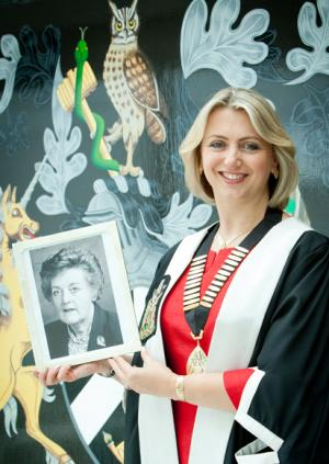Professor Helen Stokes-Lampard holding a photograph of Dr Mollie McBride
