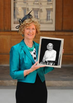 Professor Dame Margaret Whitehead holding a photograph of Dame Rosemary Rue