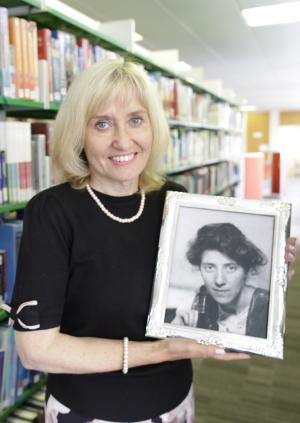 Professor Jenny Higham holding a picture of Dr Marie Stopes