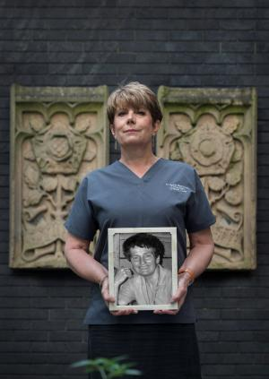 Dr Anna Batchelor holding a photograph of Dr Gillian Hanson