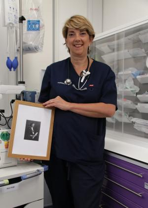 Dr Ruth Brown holding a photograph of Dr Mary Sheila Christian