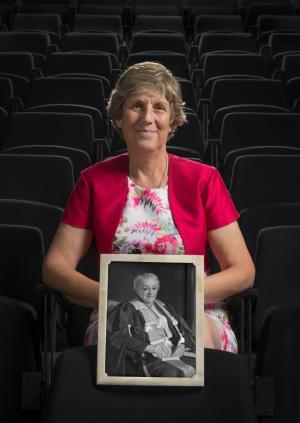 Dr Judy Evans holding a photograph of Gertrude Herzfeld