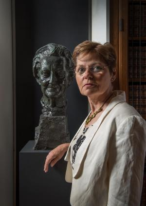 Dr Flic Gabbay standing next to a bust of Dame Cicely Saunders