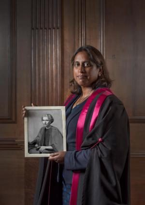 Dr Ramani Moonesinghe holding a photograph of Dr Katharine Lloyd-Williams