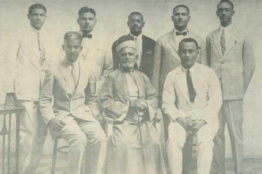 Black and white photograph of eight men seated and standing for a form photograph