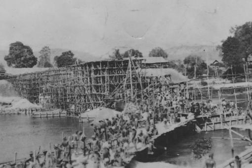 Black and white photograph of bamboo scaffolding over a large river