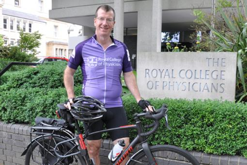 Dr Andrew Goddard stands outside the RCP main building with his bicycle