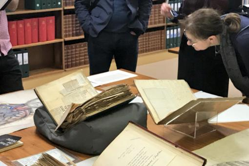 Colour photograph of people looking at a display of documents and books on a table.