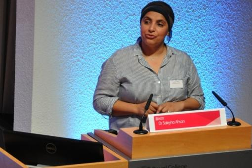 A speaker stands at a lectern delivering a presentation at the conference