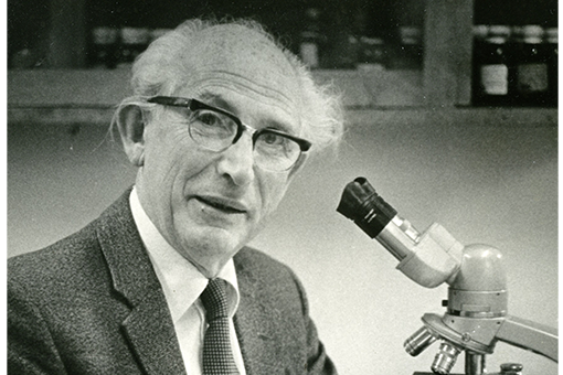 Black and white photograph of a man seated in front of a microscope.