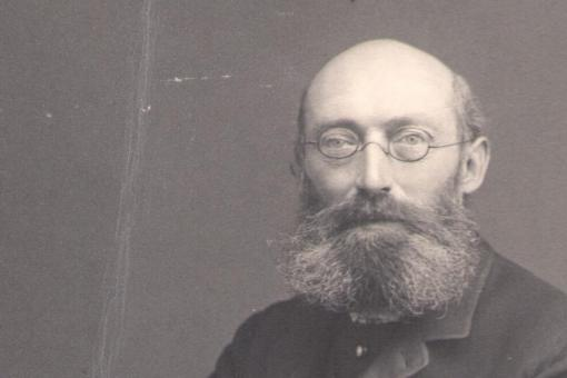 Black and white photograph of a man with a beard and glasses