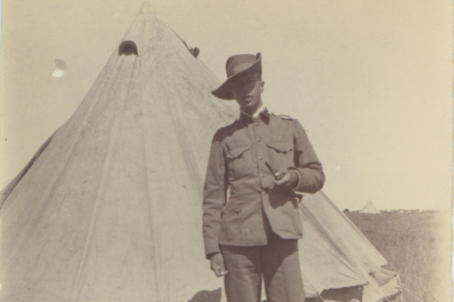 Black and white photograph of a white man in a hat holding a pipe, stood in front of a bell tent