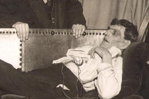 Photograph of a man lying on a couch with a microphone placed against his chest, an assistant wearing headphones leans over the back of the couch