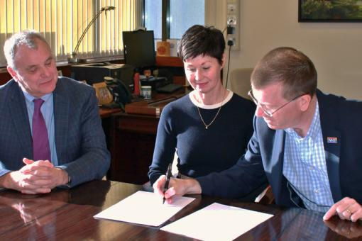 Three people sign a document while seated at a table