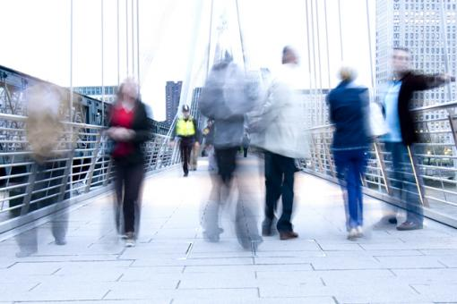 Blurred people walking over a bridge