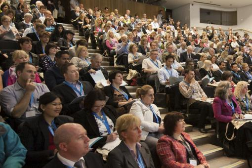 A lecture room filled with seated delegates at a previous conference