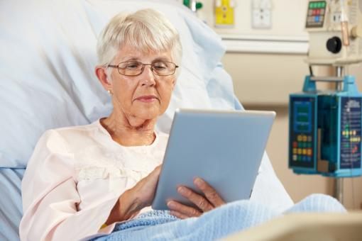 A person lying in a hospital bed using a tablet device
