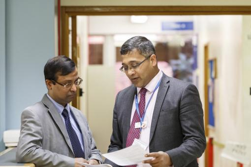 Two doctors consult papers on a hospital ward. The doctor on the left is leaning on a desk.