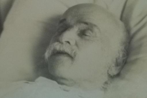 Black and white photograph of the head of a white man with a white moustache lying in a bed with his eyes closed.