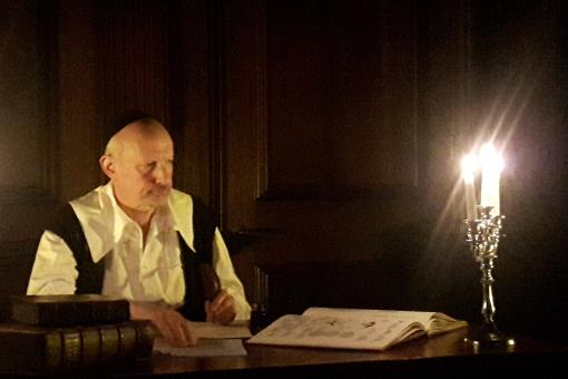 Photograph of a man in 17th century dress reading by candlelight