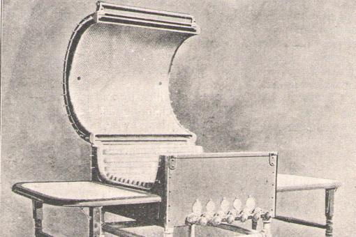 Black and white photographic diagram of a cylindrical device, hinged open